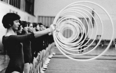 """Zentralbild Liebers 21-4-70 Gera: Frauengymnastikgruppe - Zweimal wˆchentlich treffen sich 50 Geraer M‰dchen und Frauen zwischen 13 und 23 Jahren zum Gymnastiktraining. Die Gruppe wurde in Vorbereitung des V. Deutschen Turn- und Sportfestes der DDR gegr¸ndet. Der """"holden Weiblichkeit"""" machte es soviel Spafl, dafl sie sich in der Zwischenzeit der K¸nstlerischen Gymnastik verschrieben haben. Sie treten in Sportwerbeveranstaltungen auf und gestalten Programme zu gesellschaftlichen Hˆhepunkten. Hier die Gruppe bei einer Reifen¸bung in der modernen """"Erwin-Panndorf-Halle"""". -siehe auch Foto Nr. J 0421-23-1 N-"""